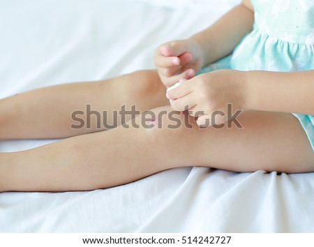 Close Up of child girl dressing wound on knee by self on the bed.