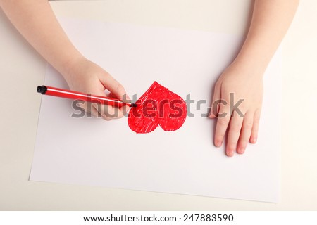 Close-up of child hands drawing a red heart - stock photo