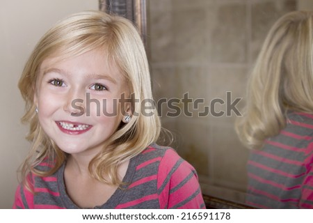 Close up of child missing her top front tooth