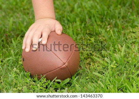 Close up of child's hand on football with room for copy - stock photo