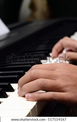Close up of Child's hands playing piano