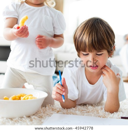 Close-up of children eating chips and drawing lying on the floor
