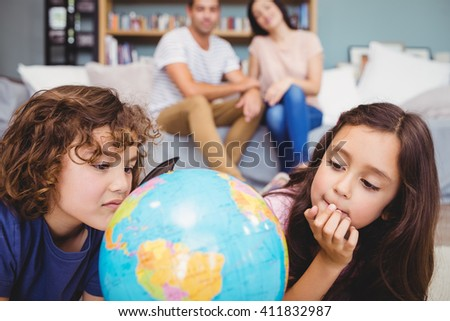 Close-up of children looking at globe against parents on sofa at home