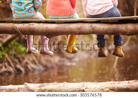 Close Up Of Children's Feet Dangling From Wooden Bridge - stock photo