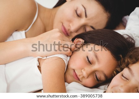 Close-up of children sleeping with mother on bed at home - stock photo