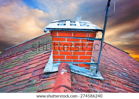 Close up of chimney on tiled roof with fungus on old worn roof tiles - stock photo