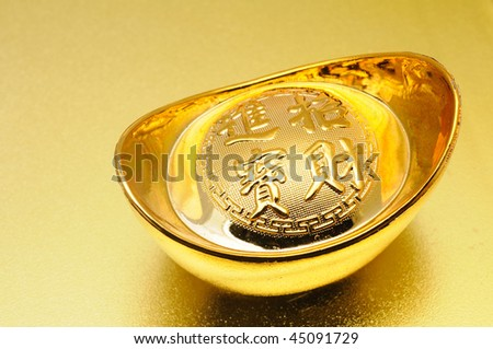 Close up of chinese gold ingot over golden background
