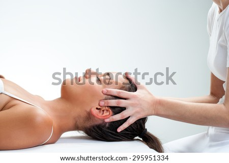 Close up of chiropractor doing healing osteopathic treatment on woman.Hands on head. - stock photo