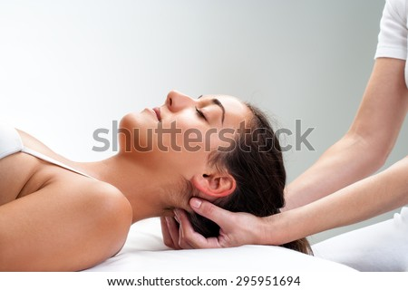 Close up of  chiropractor pressing back of head. Therapist doing healing massage with fingers at back of neck. - stock photo