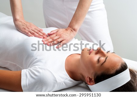 Close up of chiropractor pressing with hands on chest at reiki session. - stock photo