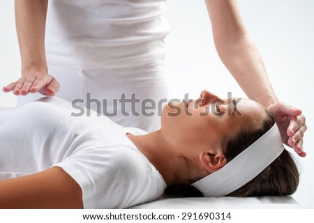 Close up of chiropractors hands doing reiki on young woman.One hand on head and one hand on chest. - stock photo