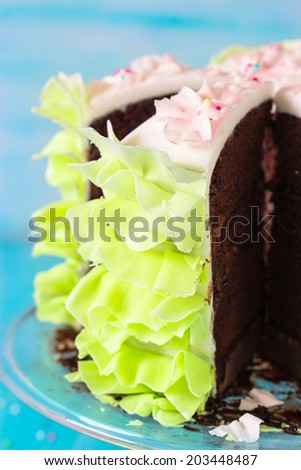 Close-up of chocolate cake decorated with fondant and cutted in pieces. Selective focus.