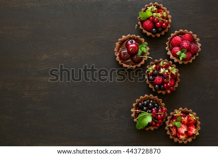 Close up of chocolate tartlets with chocolate cream, fresh strawberries, raspberries, blueberries, red currants and cherries on white wooden background. Selective focus - stock photo