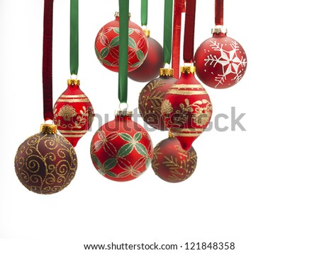Close-up of christmas baubles hanging over white background.