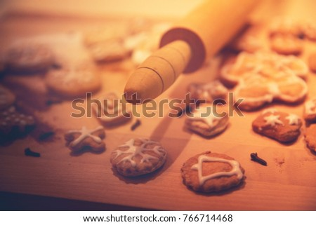 Close-up of christmas cookies and  rolling pin / Casually arranged cut-out iced cookies on wooden board