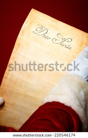 Close-up of Christmas letter held by Santa Claus - stock photo