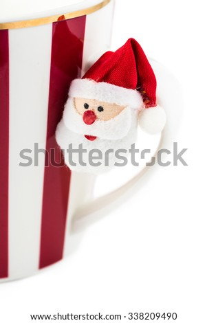 Close up of Christmas mug with hot chocolate and Santa Claus ornament on a white background.