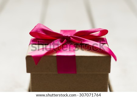 Close up of Christmas present with pink ribbon on a white wooden background - stock photo