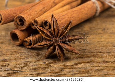Close up of cinnamon sticks and star anise on rustic wood background - stock photo