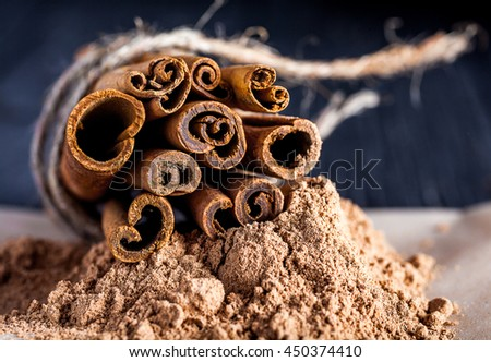Close up of cinnamon sticks linked with twine on cinnamon powder. Soft selective focus. Image in orange and yellow tones. - stock photo