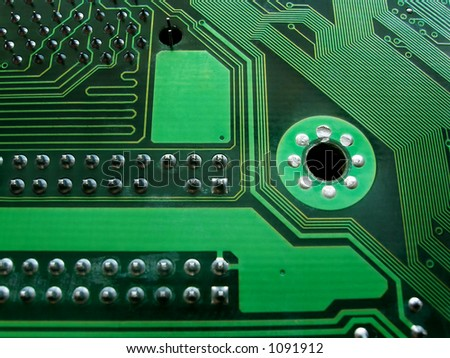 close up of circuit board with reflected points of soldering out of field of depth