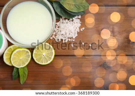 close up of citrus body lotion in bowl on wood - stock photo