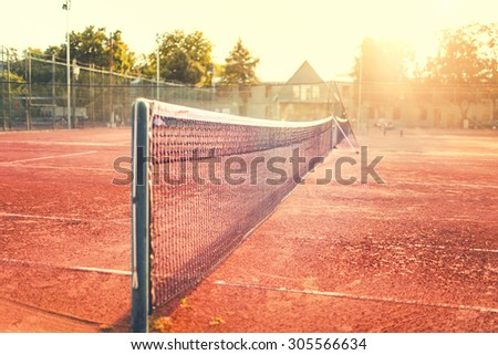 Close up of clay tennis court on a summer sunny day. Modern lifestyle with sport and fitness details - stock photo
