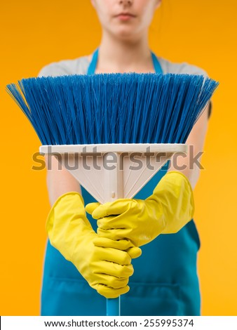 close-up of cleaning woman holding blue broom in front of her, on yellow background - stock photo