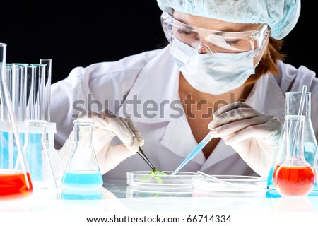 Close-up of clinician working with tools during scientific experiment in laboratory