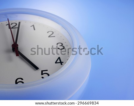 Close up of Clock showing 5 o'clock on a blue wall - stock photo