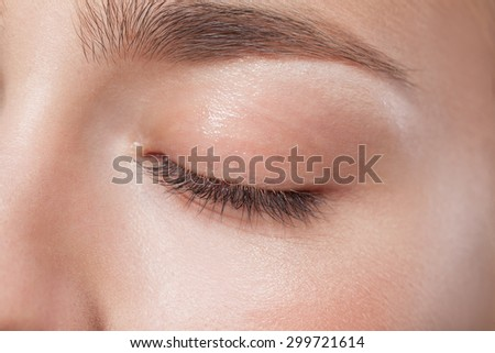 Close up of closed eye of young beautiful woman with perfect day makeup eye shadows - stock photo