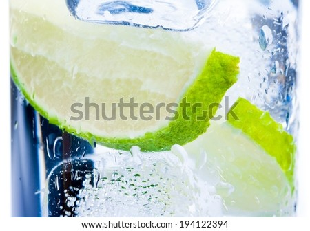 close-up of cocktail glass with ice and lime slice isolated on white background - stock photo