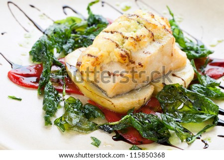 Close up of cod fish with potatoes and spinach leaves.