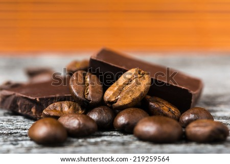 close up of coffee beans and  chocolate on brown background - stock photo