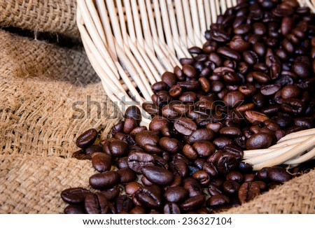 Close up of coffee beans in basket on cloth sack - stock photo