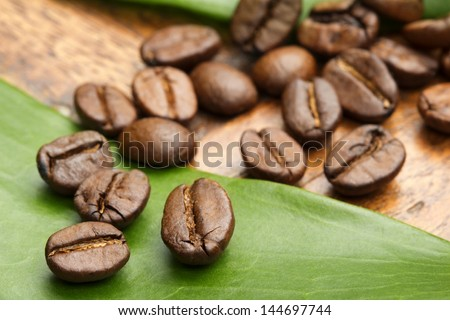 close up of coffee beans on a green leaf - stock photo