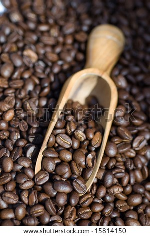 Close up of coffee beans spilling out of wooden scoop