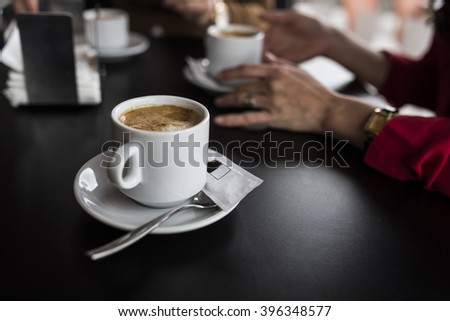 Close-up of coffee cup on plate on dark wooden table in cafe. Unrecognizable woman sitting at table on background