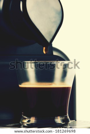 Close up of coffee machine, pouring the last drop in a cup of coffee. Vintage picture.