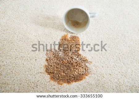 Close-up of coffee spilling from cup on carpet - stock photo