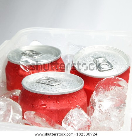 Close Up of Cola Cans in Ice with Condensation - stock photo