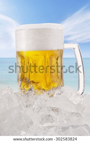 Close up of cold and fresh beer in a big glasses with ice cube, shot at the beach under clear sky - stock photo