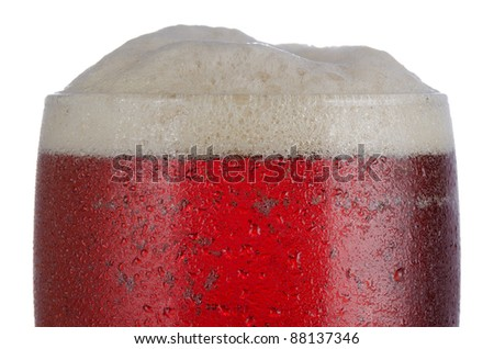 Close up of cold beer in tumbler shaped glass with head above glass rim level - stock photo