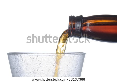 Close up of cold beer pouring into a frosted pilsner style glass showing no head - stock photo