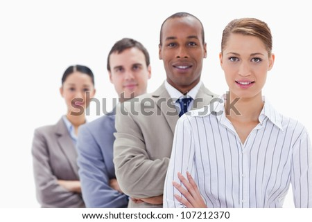 Close-up of colleagues in a single line crossing their arms with focus on the first woman - stock photo