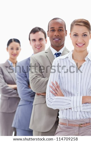 Close-up of colleagues smiling in a single line crossing their arms with focus on the first woman - stock photo