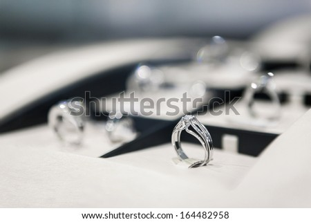 Close up of collection of rings in the showcase of jeweler's shop - stock photo