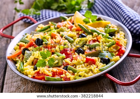 Close Up of Colorful and Fresh Vegetarian Paella Spanish Rice Dish Served in Pan with Red Handles and Linen Napkin on Rustic Wooden Table - stock photo