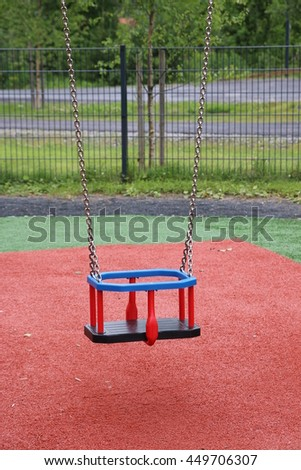 Close- up of colorful baby swing. Red and green background.