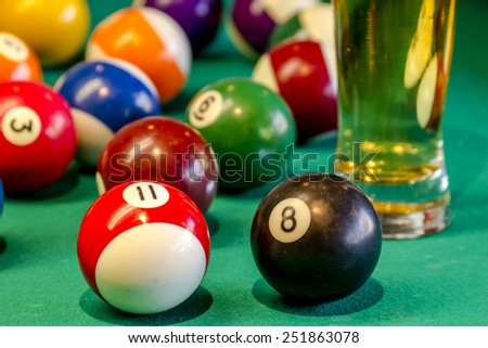 Close up of colorful billiard balls with black eight ball in front sitting on pool table with glass of beer - stock photo